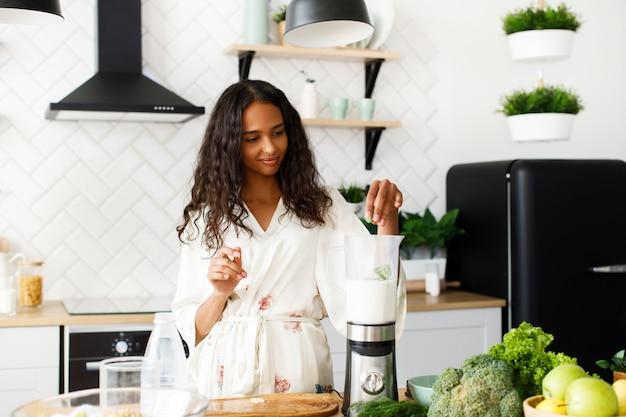 De afrikaanse vrouw maakt milkshake in een mixer in de ochtend
