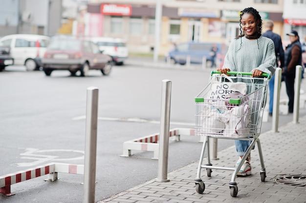 De afrikaanse vrouw met boodschappenwagentjekarretje stelde openluchtmarkt dichtbij autoparkeren.