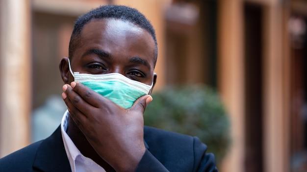 De afrikaanse zakenman draagt medisch masker voor bescherming tegen coronavirus of covid-19