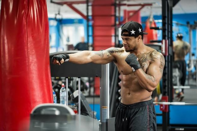De afrikaanse zwarte mannelijke bal die van het bokserponsen bokshandschoenen in gymnastiek dragen