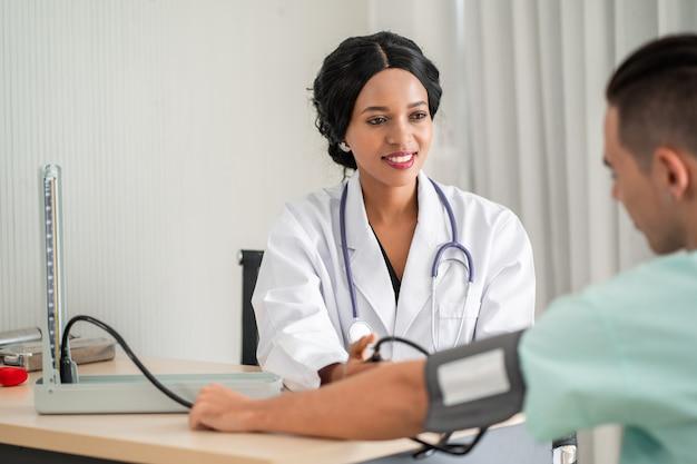 De afro-amerikaanse arts meet de bloeddruk voor de patiënt. en zorg voor consultatie over behandeling aan patiënten die in een rolstoel zitten en nauwlettend volgen