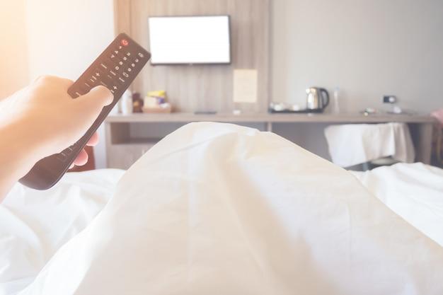 De afstandsbedieningtelevisie van de handholding op bed in slaapkamer dichte omhooggaand op ver