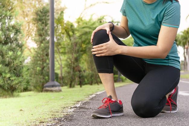 De agent van de geschiktheidsvrouw voelt pijn op knie. outdoor oefening activiteiten concept
