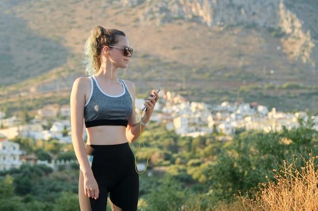 De agentmeisje van de tienergeschiktheid met smartphone in oortelefoons op bergweg