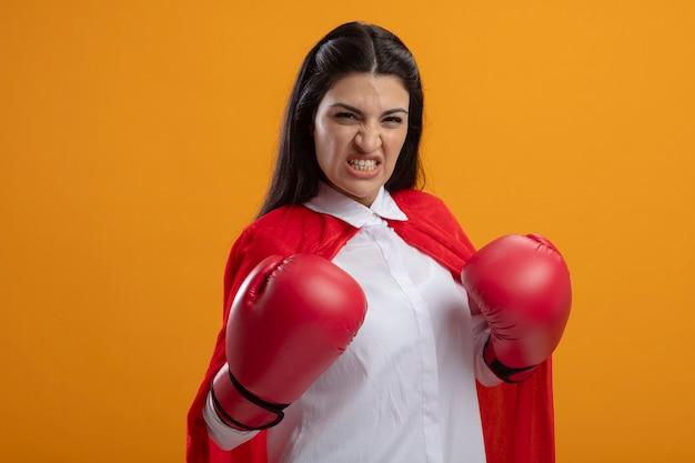 De agressieve jonge supervrouw die dooshandschoenen draagt die voorzijde het houden bekijkt dient lucht in die op oranje muur wordt geïsoleerd