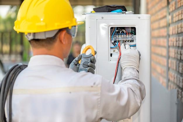 De airconditionermonteur controleert het luchtcompressorsysteem