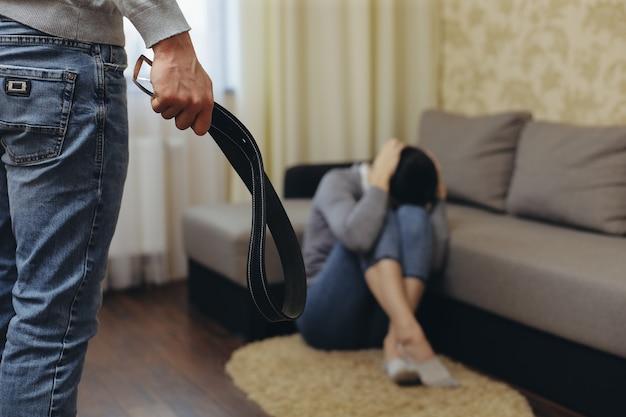 De alcoholische echtgenoot slaat zijn vrouw met een riem. zhenzhina bedekt zichzelf met haar handen. geweld in familie