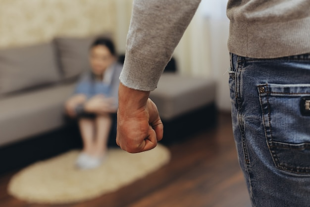 De alcoholische echtgenoot slaat zijn vrouw met zijn vuist. zhenzhina bedekt zichzelf met haar handen. geweld in familie