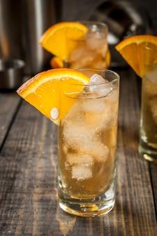 De alcoholische oranje highballcocktail van de wodkawisky met een sinaasappel versiert, op houten lijst copyspace