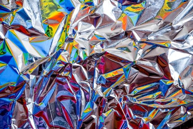 De aluminiumfolie van de regenboog verfrommelde zilveren textuur abstracte achtergrond
