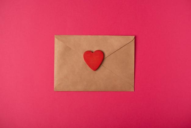 De ambachtelijke envelop met rood hart op de hete roze achtergrond. valentijnsdag concept.
