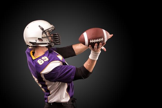 De amerikaanse bal van de voetbalsterholding in van hem dient rook in. het concept van american football, motivatie, kopie ruimte