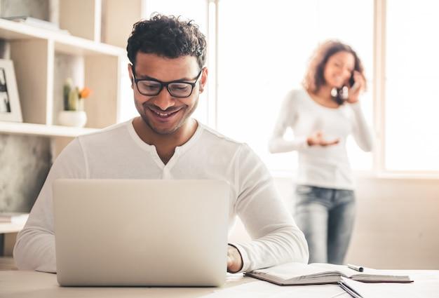 De amerikaanse zakenman van afro gebruikt thuis laptop.