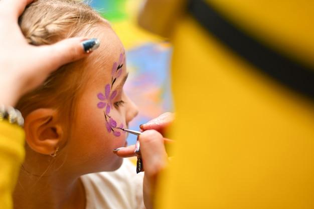 De animator schildert het gezicht van het kind