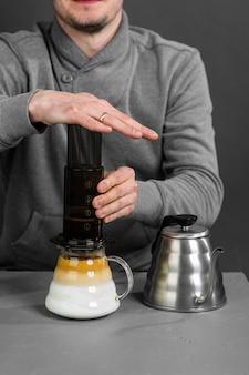 De anonieme man van de barista brouwt koffie volgens een speciale filtratiemethode.