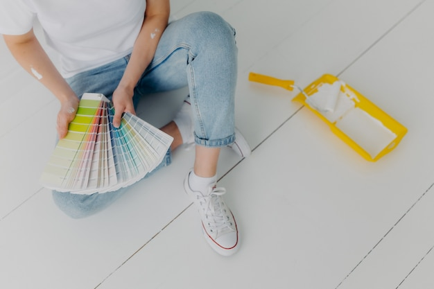 De anonieme vrouw in jeans houdt kleurstalen, kiest de beste toon voor renovatiewanden