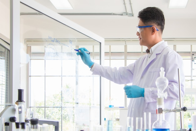 De apotheker schrijft een formule om de combinatie van medicijnen te testen tegen een nieuwe stam van het coronavirus