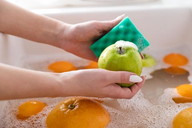 De appel van de vrouwenwas met een spons in de gootsteenkeuken, die vruchten in zeepachtig water grondig doorweken wast grondig