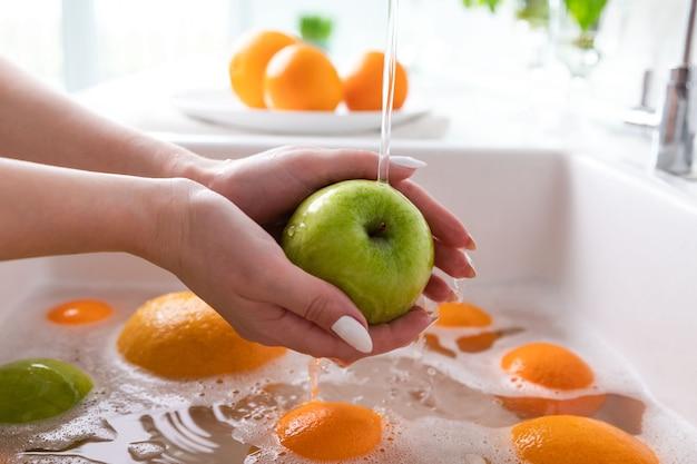 De appel van de vrouwenwas onder kraan in de gootsteenkeuken, doorwekend fruit in zeepachtig water grondig wast