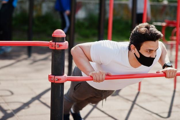 De arabische mens van portretsporten in zwart medisch gezichtsmasker die trainingoefeningen doen in openluchtgymnastiekplaats tijdens coronavirusquarantaine.