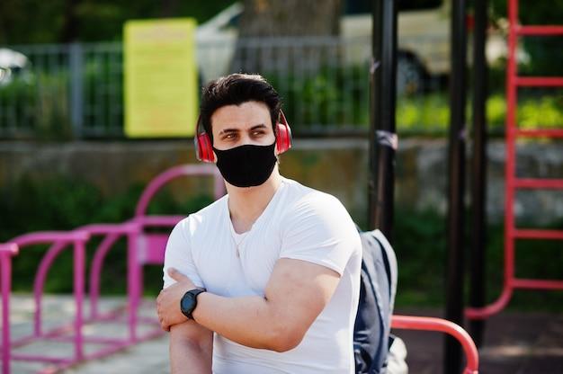 De arabische mens van portretsporten in zwart medisch gezichtsmasker stelde openlucht met oortelefoons tijdens coronavirusquarantaine.