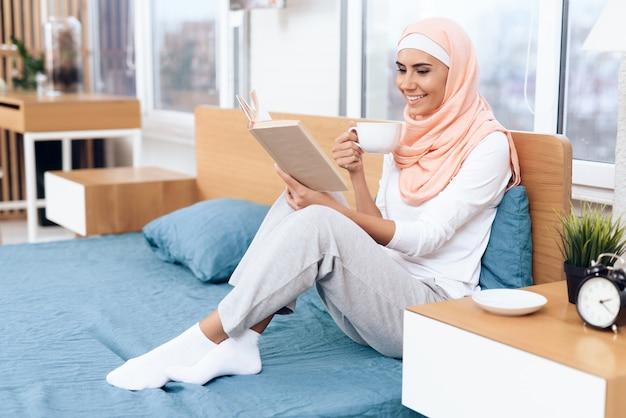 De arabische vrouw drinkt thee en leest een boek.