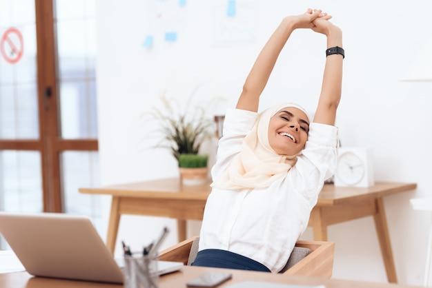 De arabische vrouw in de hijab ontspant zich.