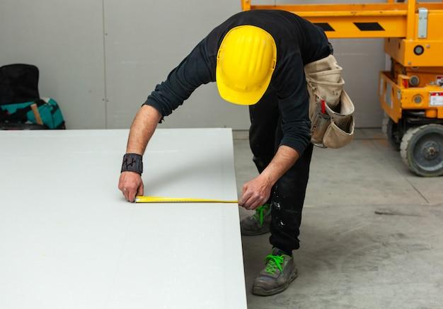 De arbeider bouwt een gipsplaatmuur.