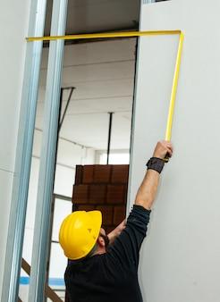 De arbeider bouwt een gipsplaatmuur