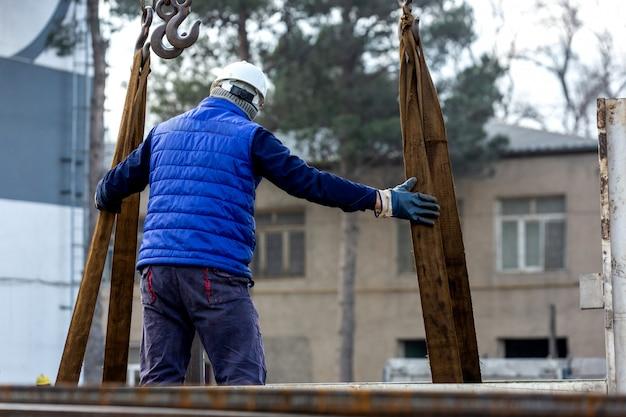 De arbeider controleert lading op kraan