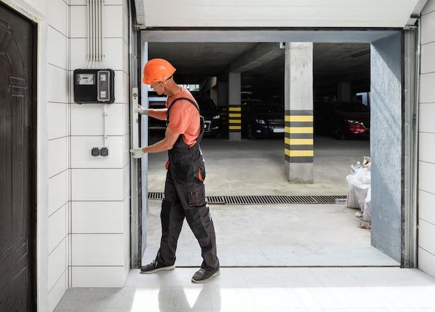 De arbeider controleert met het waterpeil de verticale geleider van de liftdeur.