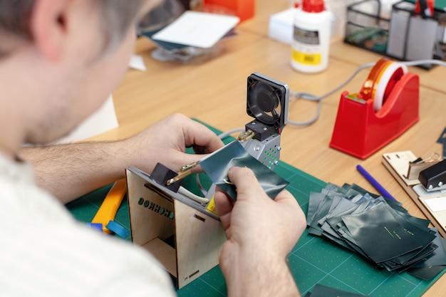 De arbeider die de randen van labels en labels voor kleding afsnijdt op de elektrische touwsnijder met een verwerking op hoge temperatuur;
