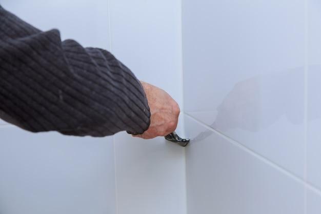 De arbeider die tegelzetter op de muur met troffel herstelt
