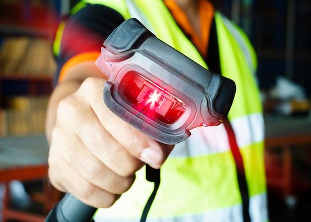 De arbeider die van de pakhuisarbeider streepjescodescanner met aftasten rode laser houden. voorraadbeheer van magazijnen.
