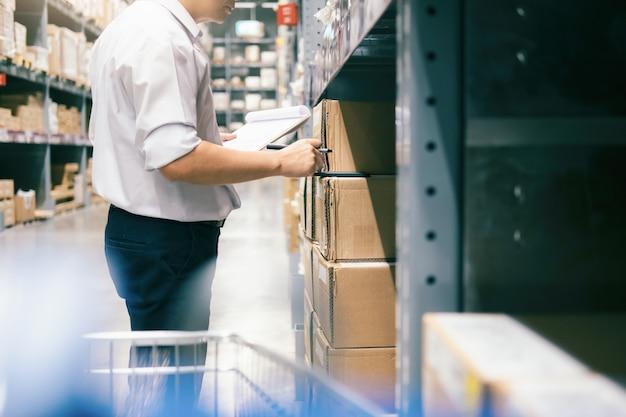 De arbeider die van het mensenpakhuis goederen controleren bij pakhuis.