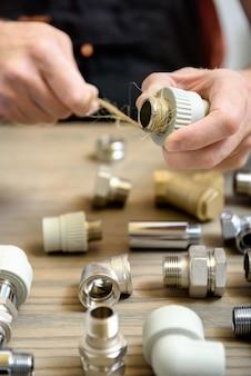 De arbeider gebruikt de hennepvezels van een loodgieter.