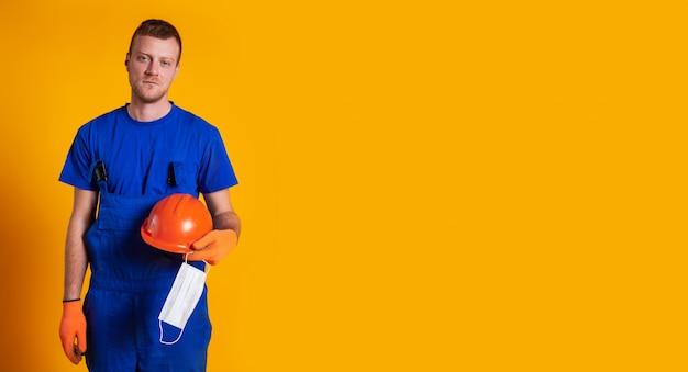 De arbeider in bouwoverall en handschoenen op een gele achtergrond, houdt een beschermende helm en een medisch masker in zijn hand.