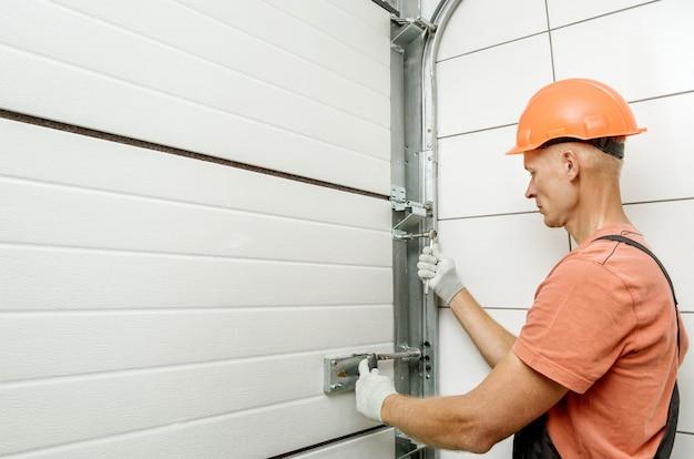 De arbeider installeert liftpoorten in de garage.