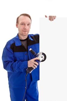De arbeider met hoekmolen in zijn hand die leeg tekenaanplakbord houdt