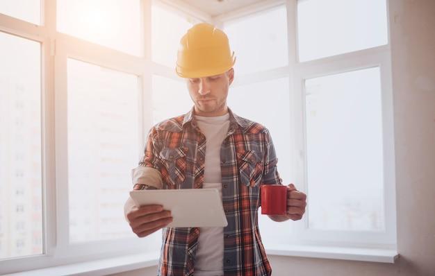 De arbeider of bouwer houdt een kopje koffie in zijn handen en kijkt naar de tablet. tegen de achtergrond van bouw en reparatie.