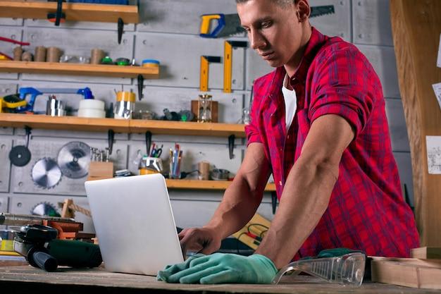 De arbeider op zijn werkplaats werkt met notitieboekje terwijl en status op fabrieksworkshop