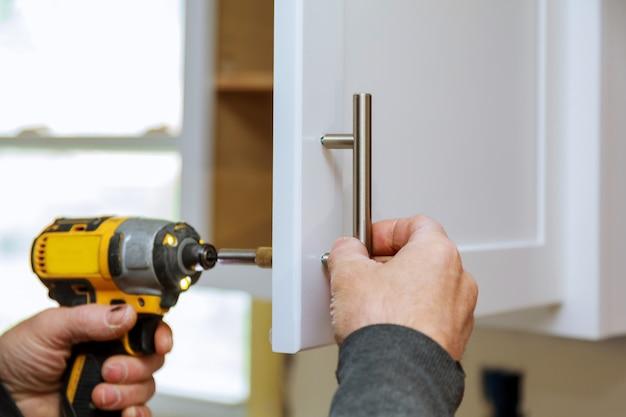 De arbeider plaatst een nieuwe handgreep op de witte kast met een schroevendraaier