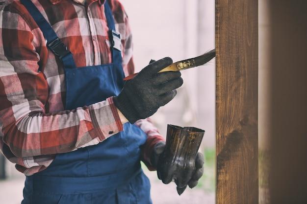 De arbeider schildert het houten terras