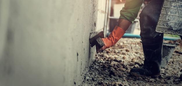 De arbeider van de close-up het pleisteren cement op muur voor de bouw van huis