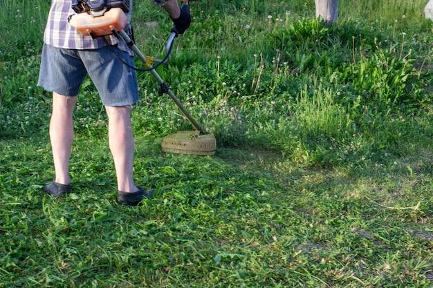 De arbeider van een tuin snijdt een gras af. de man in een uniform van de algemene arbeider werkt op een grasveld. werk van gemeentelijke diensten aan verbetering van territoria.