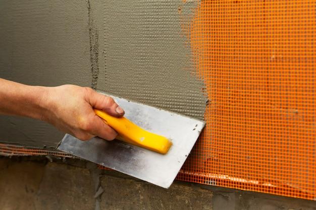 De arbeider voert de versterking en het vullen van de muren uit. selectieve aandacht.