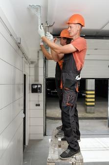 De arbeiders installeren liftpoorten in de garage.