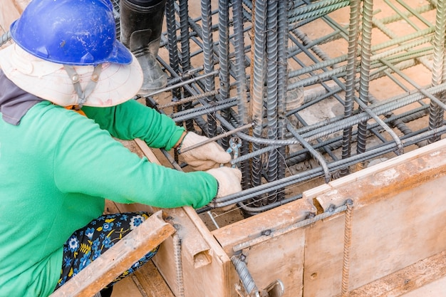De arbeiders overhandigen gebruikend staaldraad en tangen om rebar te beveiligen