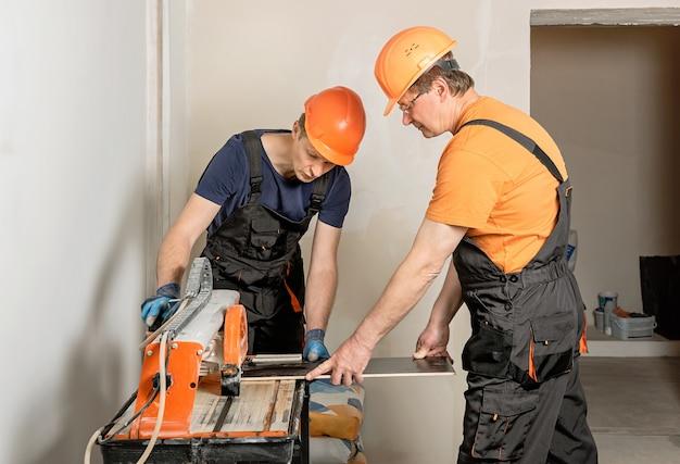 De arbeiders snijden een keramische tegel op een natte zaagmachine