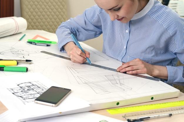 De architect bereidt het ontwerp van het gebouw voor en tekent een tekening op wit papier